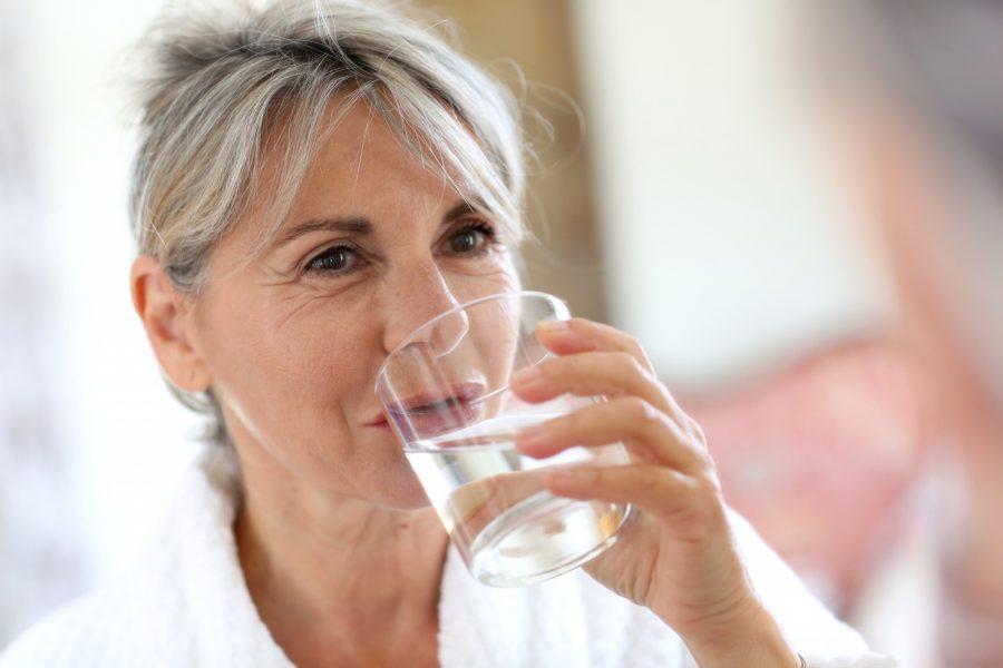 Женщина пьет из стакана